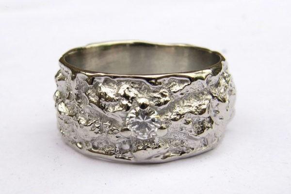 Alliance créateur texture irrégulière or blanc et diamant serti griffes centré