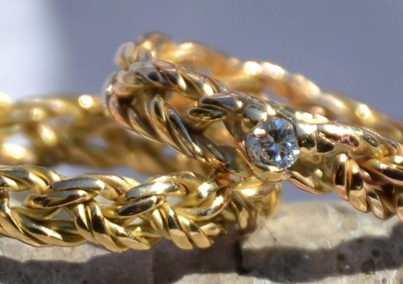 Couple d'alliances tressées 3 brins 3 ors avec diamant et 3 brins or jaune - vue rapprochée